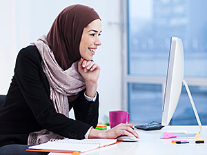 Arabic woman working on computer.